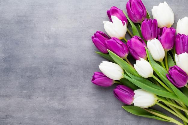 色とりどりの春の花、灰色の表面にチューリップ。