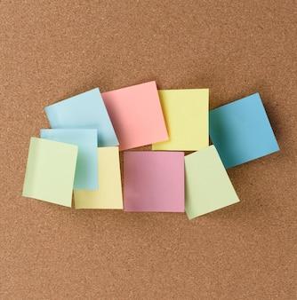 여러 가지 빛깔의 정사각형 스틱이 갈색 코르크 질감, 복사 공간에 붙어 있습니다.