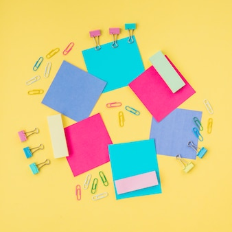 Multicolored sticky notes and paper clip on yellow surface
