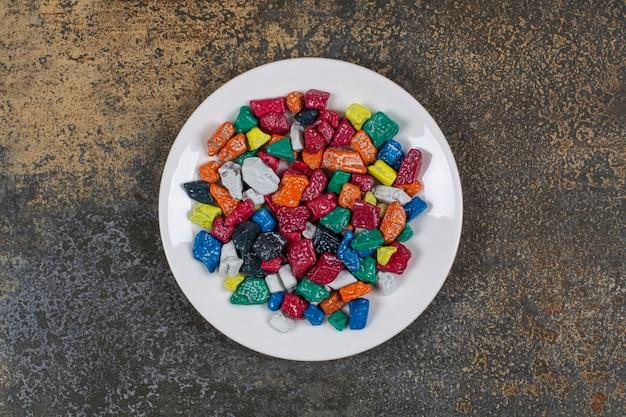 흰색 접시에 여러 가지 빛깔 된 돌 사탕입니다.