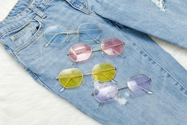 Multicolored sunglasses on  jeans