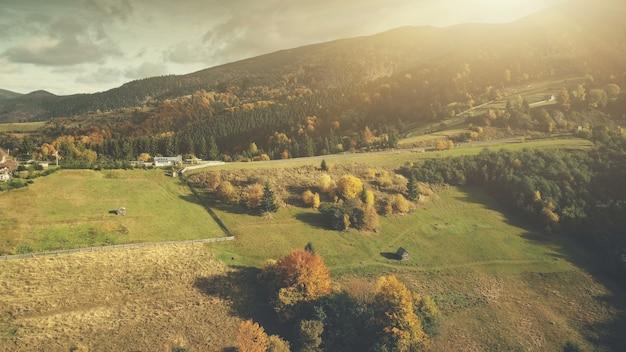 色とりどりの夕日秋の高原の風景空撮壮大なカルパティア山脈の牧草地のコテージ