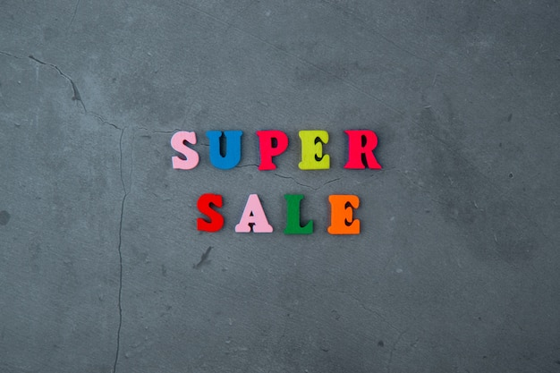 The multicolored super sale word is made of wooden letters on a grey plastered wall