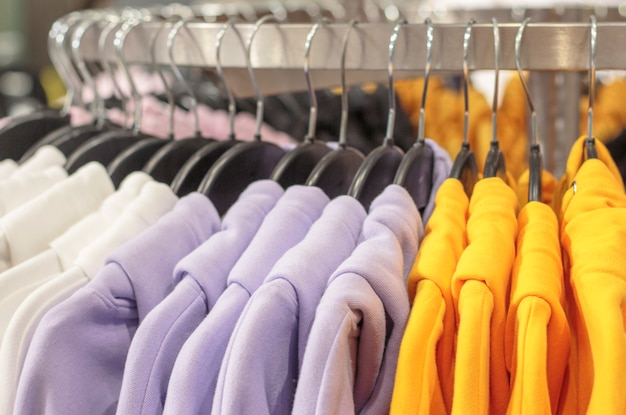 Multicolored sweatshirts hang on a hanger in store close-up.