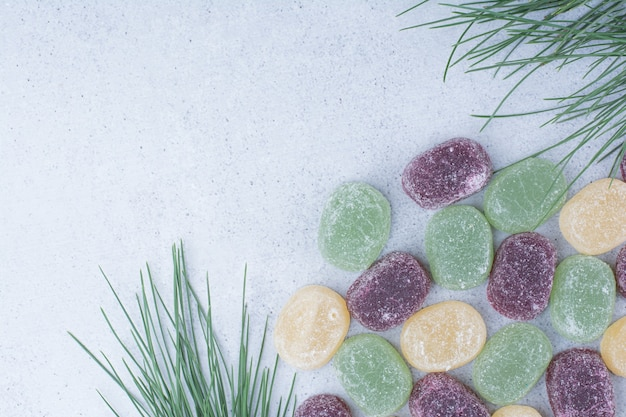 Multicolored sweet marmalades on marble background.