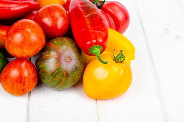 Разноцветные сладкие перцы и помидоры на деревянном столе. студийное фото.
