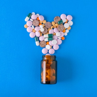 Multicolored tablets are poured from a glass vessel in the shape of a heart on a blue background. the view from the top. the concept of treatment and prevention of diseases. flat lay.