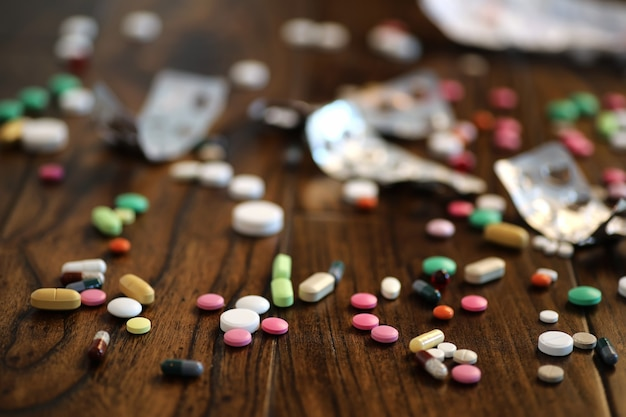 Multicolored tablets of different shapes and sizes on the wooden floor