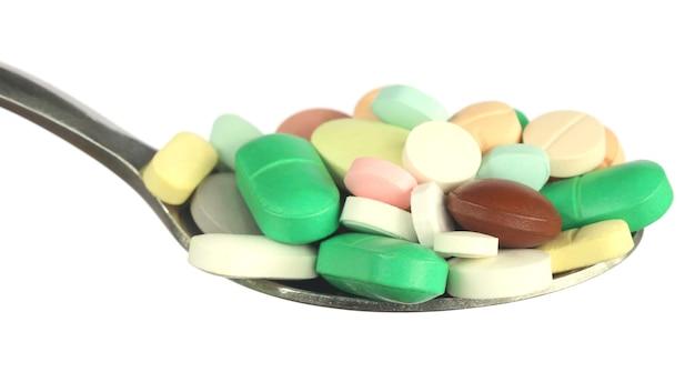 Разноцветные таблетки на серебряной ложке на белом фоне