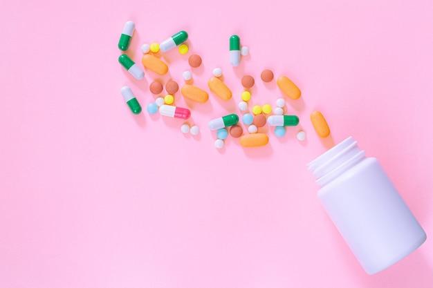 분홍색 배경에 플라스틱 병에 여러 가지 빛깔의 정제 알약 캡슐