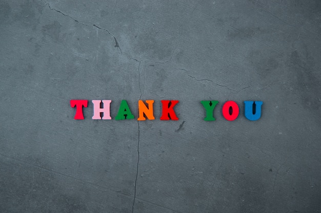 The multicolored thank you word is made of wooden letters on a grey plastered wall.