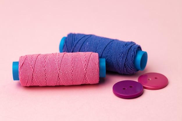 Разноцветные катушки с нитками и кнопки на розовом фоне