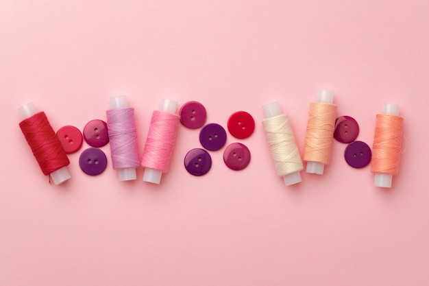 Multicolored thread spools and buttons on pink background