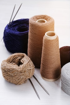Multicolored threads, skeins and tangles of italian wool yarn, knitting needles. the concept of knitting, needlework, handmade.