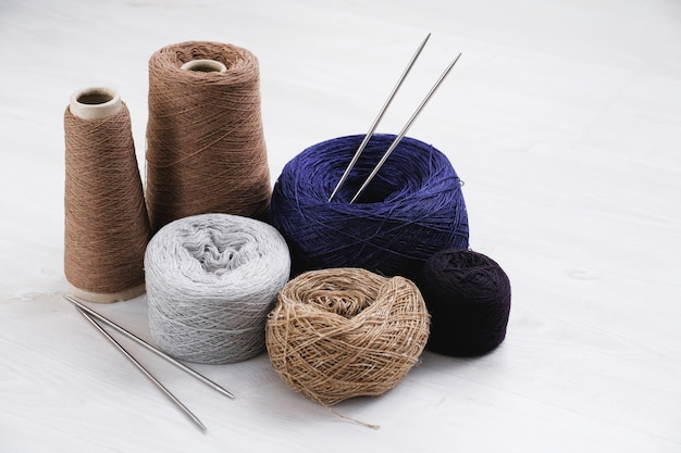 Multicolored threads, skeins and tangles of italian wool yarn, knitting needles