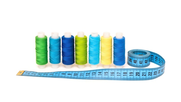 Multicolored threads with needles and tape measure on a white background.