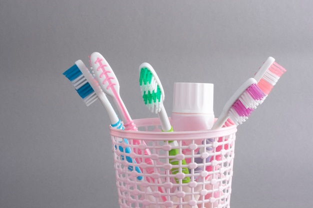 Multicolored toothbrushes in a plastic cup