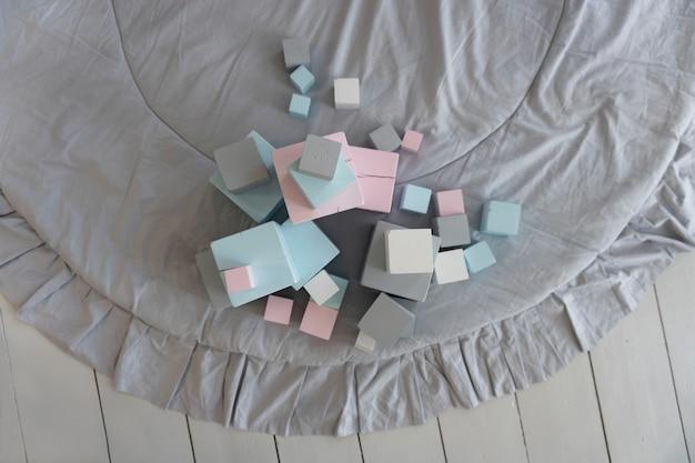 子供部屋のカーペットの上のパステルカラーの色とりどりのおもちゃの立方体、上面図