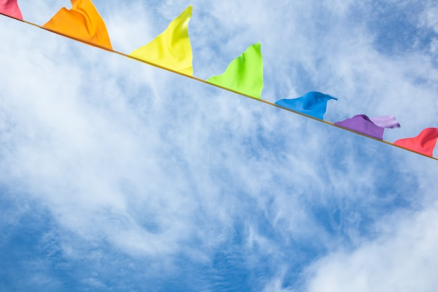 Multicolored triangular flags develop against a blue sky with light clouds.