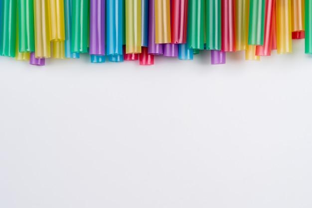 Разноцветные трубы заделывают профиль в ряд для фона с копией пространства. соломинки пластиковый напиток