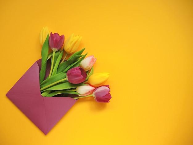 Разноцветные тюльпаны в фиолетовом конверте на женский день или пасху на желтом фоне