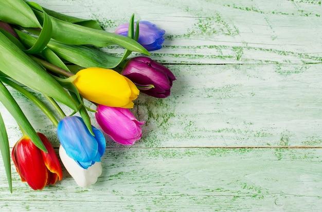 ぼろぼろの緑のテーブルに色とりどりのチューリップ。花の虹