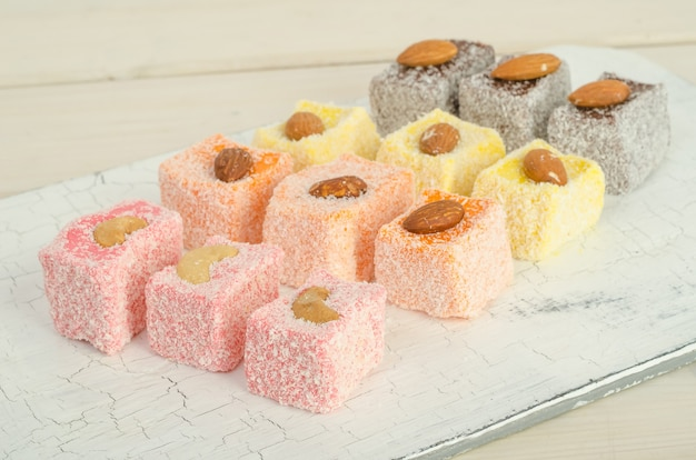 Multicolored turkish delight, lokum with different flavors and nuts on a white board close up with selective focus