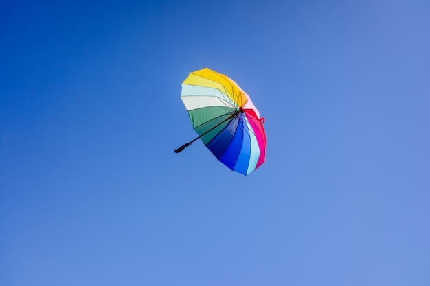 Multicolored umbrella flying suspended over bright blue sky background