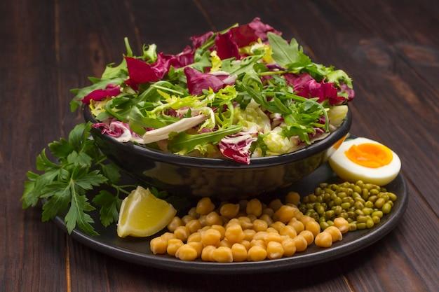 검은 접시에 여러 가지 빛깔의 야채 믹스, 병아리 콩, 녹두, 계란, 토마토. 균형 잡힌 영양. 어두운 배경