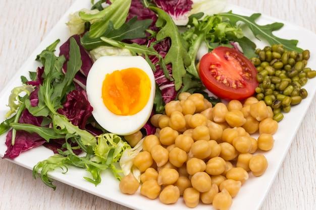 검은 접시에 여러 가지 빛깔의 야채 믹스, 병아리 콩, 녹두, 계란, 토마토. 균형 잡힌 영양. 흰색 배경
