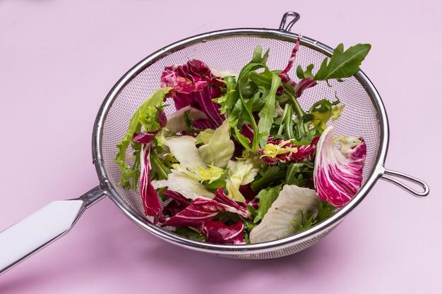금속 소쿠리에 여러 가지 빛깔의 야채 믹스. 비건 음식. 깨끗한 식사. 분홍색 배경