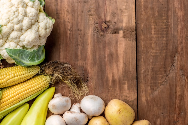 The multicolored vegetables on wooden table background