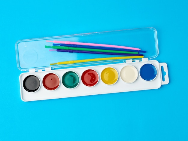 Разноцветные акварельные краски в пластиковой коробке и кисточки на синем фоне