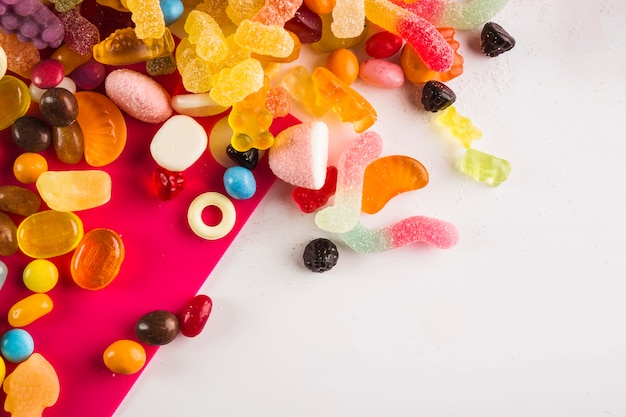 Multicolored winegums on white and fuchsia background