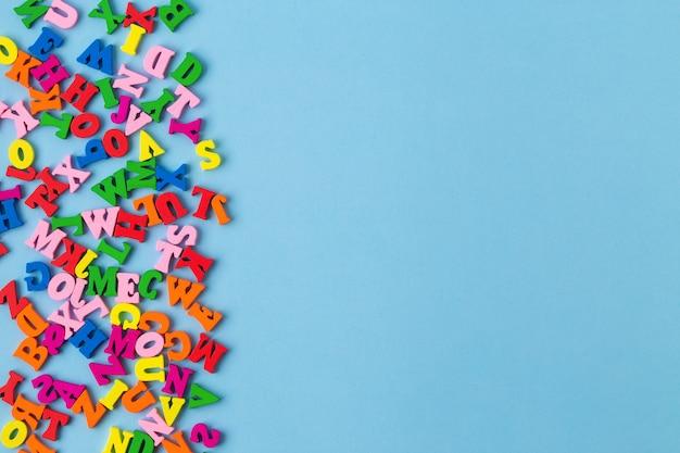 Разноцветные деревянные буквы на синем фоне. вид сверху