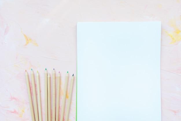 ピンクの色とりどりの木の鉛筆と紙のシーツ