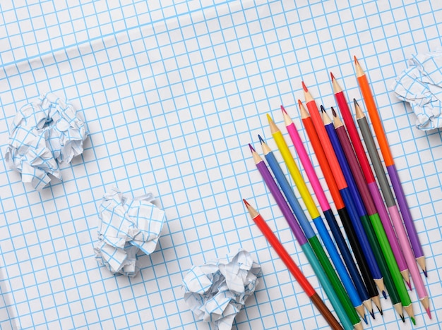 Multicolored wooden pencils and crumpled sheets of paper on white squared paper background, top view
