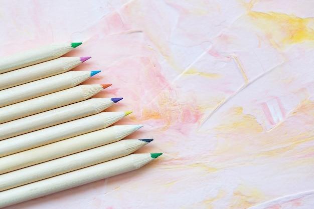 ピンクの背景に色とりどりの木製の鉛筆。描画、創造的な芸術または学校のコンセプトに戻って、コピースペース