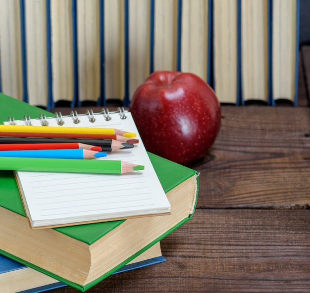 Multicolored wooden pencils and a red apple