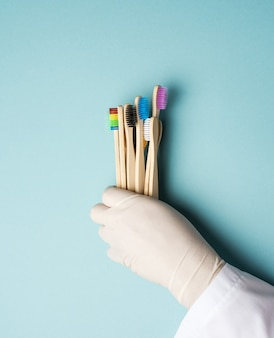 Multicolored wooden toothbrushes on a blue surface, plastic rejection concept, zero waste