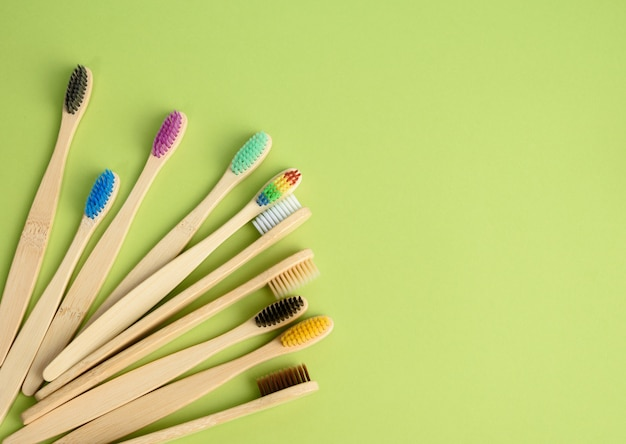 Multicolored wooden toothbrushes on a green background, plastic rejection concept, zero waste, top view