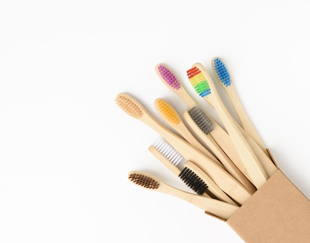 Multicolored wooden toothbrushes on a white background, plastic rejection concept, zero waste, close up