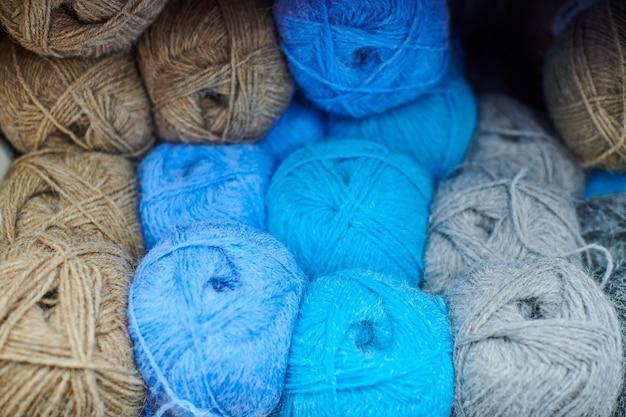 뜨개질 가게 센터에 있는 여러 가지 빛깔의 원사 공. 뜨개질을위한 많은 색상 원사. 상점 앞, 매크로에 화려한 파란색, 갈색, 회색 털실.