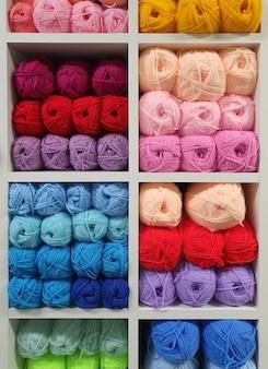 잡화 가게의 선반에 뜨개질을하기위한 여러 가지 양모 원사. 니트 공예품 개념