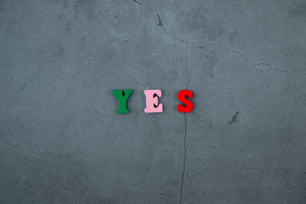 The multicolored yes word is made of wooden letters on a grey plastered wall.