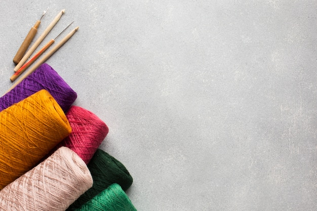 Multicoloured big sewing threads and grey copy space background