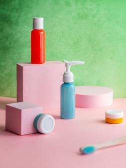 핑크 장식과 녹색 벽에 칫솔과 여러 가지 빛깔의 병 및 항아리