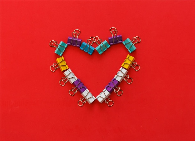 Multicoloured metal office paper clips forming heart shape on red background. concept valentine day.