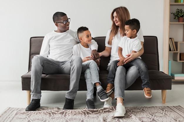 多文化家族が一緒にソファで過ごす