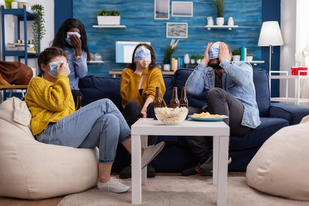 Multicultural friends intimidated looking at scary movie during coronavirus pandemic wearing face mask to prevent illness covering faces sitting on sofa living room.
